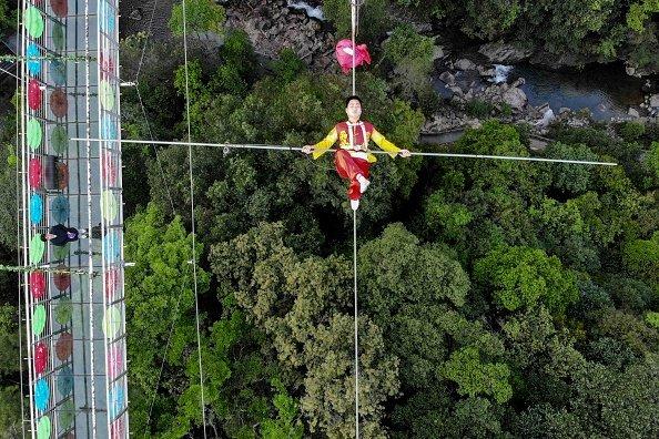 An acrobat performs over Jiulong River