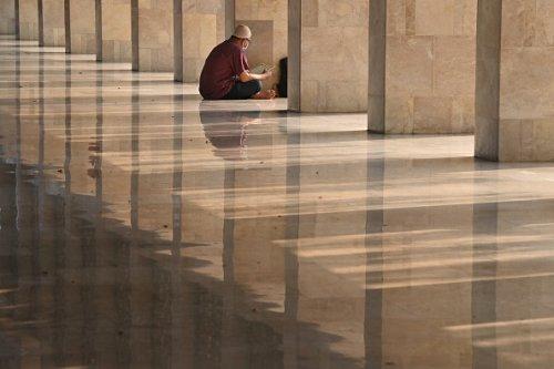 Un uomo musulmano legge una copia del Corano durante il Ramadan