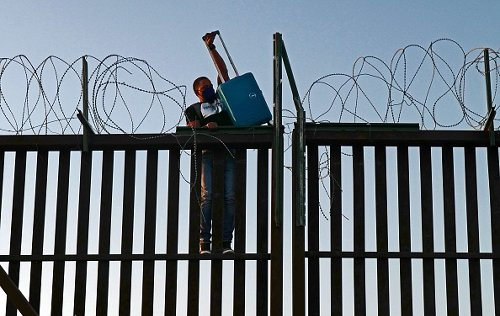 A man attempts to cross over a fence