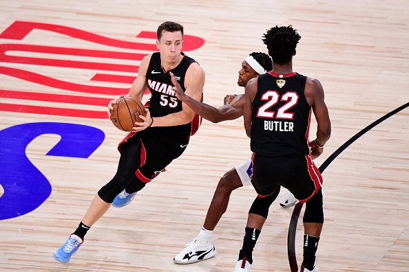 Duncan Robinson of the Miami Heat drives the ball as Jimmy Butler of...