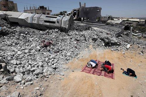 Fedeli musulmani palestinesi pregano tra le macerie di una moschea a Beit Lahia