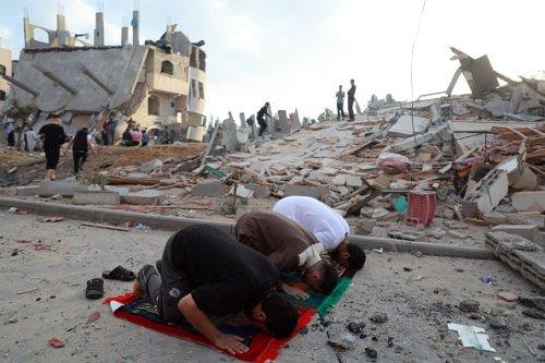 Uomini musulmani palestinesi pregano in mezzo alla macerie