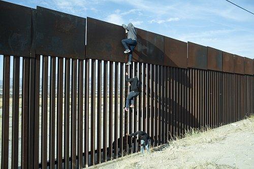 Men scaling border wall