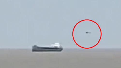 Silver UFO Can Be Seen Stalking Behind A Cargo Ship