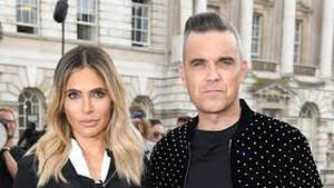Family first: Robbie and Ayda Williams will travel to Hawaii for their daughter's first birthday so they can celebrate with her surrogate