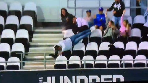 Fan falls over empty seats while catching Livingstone's massive six, manages to save his phone - VIDEO