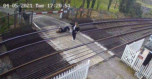 Urgent warning as girl seen lying on train tracks using her phone