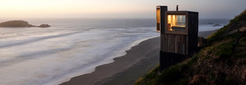 Two holiday cabins on stilts sit lightly by the ocean