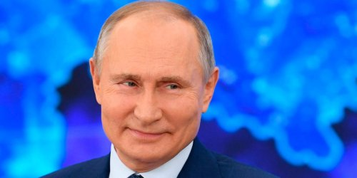 Russian President Vladimir Putin laughs at a reporter who asked if he was a 'killer'