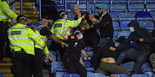 Opposing fans launched missiles, threw punches, and whipped each other with belts in a violent clash after a Europa League match