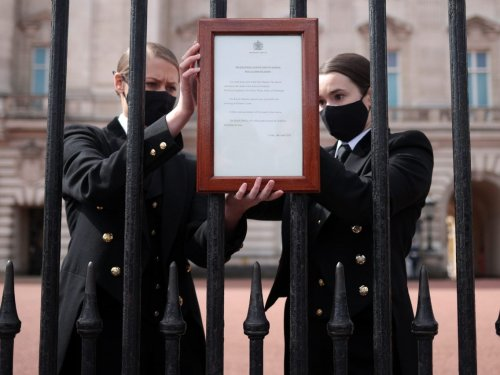 Photos show Buckingham Palace staff hanging a sign on its front gates announcing Prince Philip's death