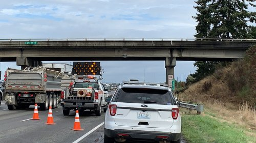 Truck hauling an excavator hits I-5 overpass in Everett
