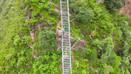 Man Attempts to Climb an Incredibly Steep Steel Ladder 2,600 Feet Up a Mountainside in Sichuan, China