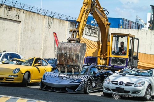 $1.2 million worth of 'contraband' Bentley and McLaren supercars are bulldozed and crushed by the Philippines Bureau of Customs