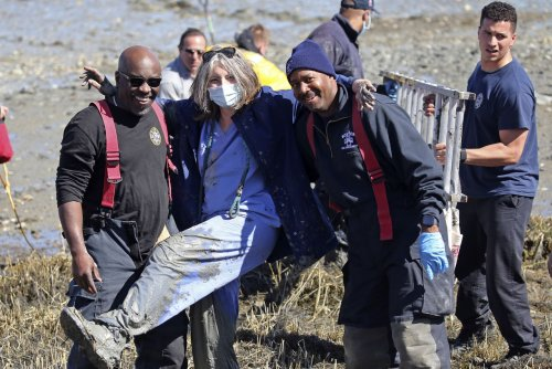 Nurse, capturing the feeling of a nation, gets stuck in mud at Boston's Constitution Beach