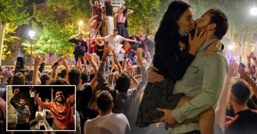 Couple kiss in street as thousands celebrate end of lockdown in Spain