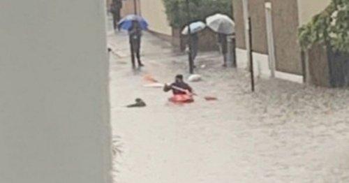 Man rows down flooded UK street in orange kayak as bemused residents look on