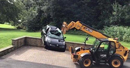 JCB driver dumps car outside plush apartments 'in bitter row over unpaid bill'