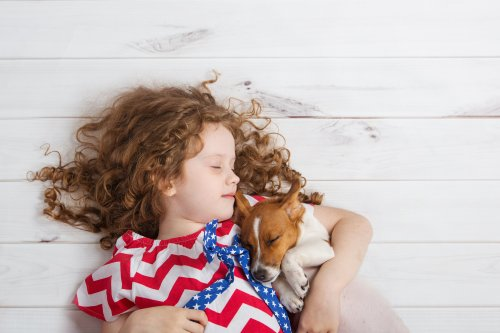 Girl and dog look identical as they snooze together in hilarious video