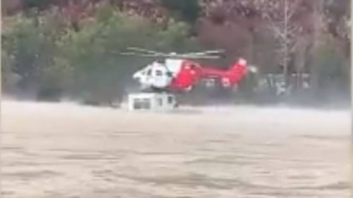 Watch: Rescue helicopter plucks traveller from roof of campervan in flooded river - NZ Herald