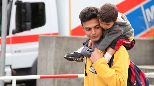 "Ahmed and his family came to Munich from Syria. He is carrying his young cousin. He came to Germany ""for studying, good work, and to get married and have a baby from [a] German."""
