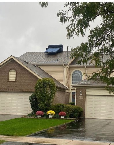 Man unamused by couch someone put on his home's roof