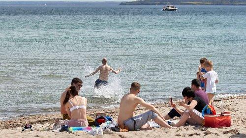Sommer im Norden: Touristen baden schon in der Ostsee