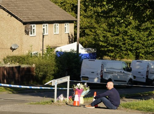 Distraught father leaves flowers at scene where four people found dead