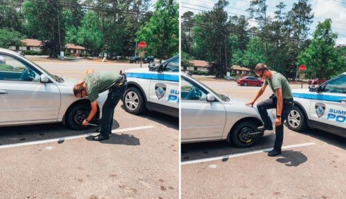 Officer helping driver with flat tire in the middle of a road in Summerville