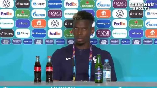 Paul Pogba, a devout Muslim, removes a bottle of Heineken beer from the press table after France's win over Germany.