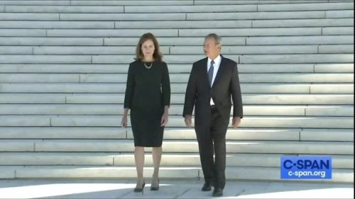 Justice Amy Coney Barrett and Chief Justice John Roberts pose for a photo op outside the Supreme Court.