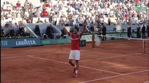 Novak Djokovic celebrates winning the French Open, his 19th Grand Slam, and gives his racket to a lucky young fan.