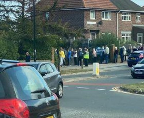 A photograph was taken to show a long line of elderly men and women queuing for their booster jabs