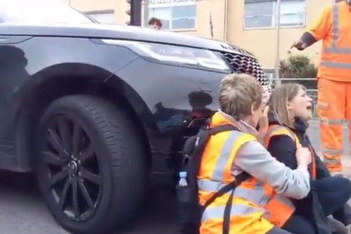 Dramatic moment furious motorist drives into eco-protesters blocking the road