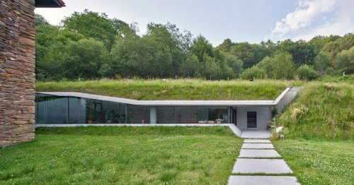 A sleek glass-and-concrete addition built into a hill