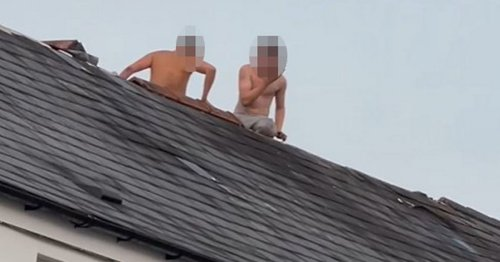 Police cordon off street as two topless men climb onto pub roof and smash tiles