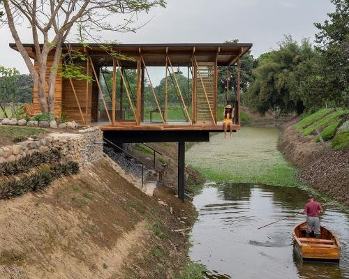 Natura Futura Arquitectura raises timber-framed tea room over a water channel in Ecuador