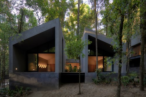 These volcanic stone cabins merge with the pre-existing trees to minimize the home's footprint!