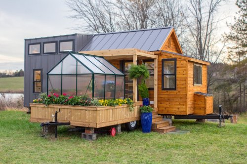 This tiny home inspired by Scandinavian design comes with a small greenhouse and a porch swing!