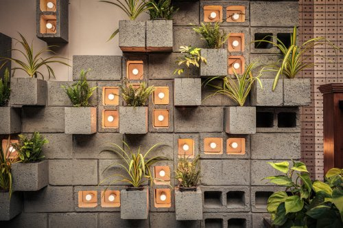 This concrete restaurant merges brutalist architecture with a vertical garden design for an inviting green vibe!